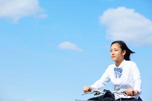 風を切って自転車に乗る女子高生の写真素材 [FYI01463911]