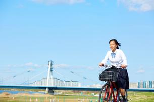 河川敷を自転車で走る女子高生の写真素材 [FYI01463912]