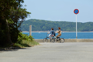 海沿いで自転車をこぐ2人の女性の写真素材 [FYI01463929]