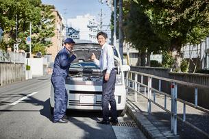 ボンネットを開けた車の前でこちらを見る二人の男性の写真素材 [FYI01463931]