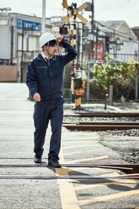線路を渡る作業服とヘルメットの男性の写真素材 [FYI01463937]
