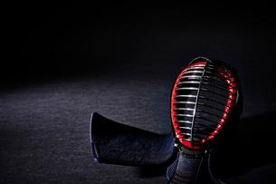 黒い背景に置かれた剣道の面の写真素材 [FYI01463941]