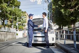 車の前で握手する二人の男性の写真素材 [FYI01463944]