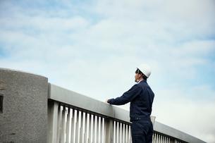 遠くを見ている橋の上の作業服の男性の写真素材 [FYI01463957]