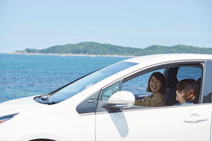 海の前を白い車でドライブする女性の写真素材 [FYI01463972]