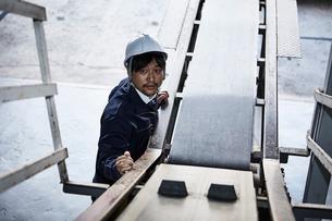 ベルトコンベアーを見上げている作業服とヘルメットの男性の写真素材 [FYI01463981]
