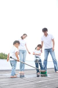 屋上を掃除する家族の写真素材 [FYI01463993]
