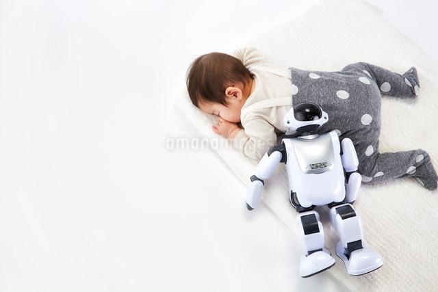 お昼寝する赤ちゃんに添い寝するロボットの写真素材 [FYI01464002]