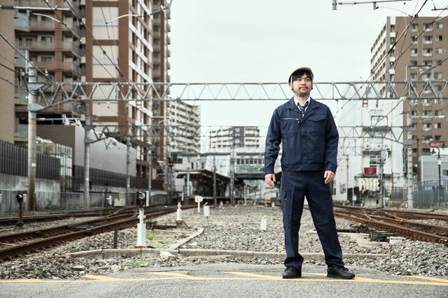 線路に立つ作業服とヘルメットの男性の写真素材 [FYI01464009]