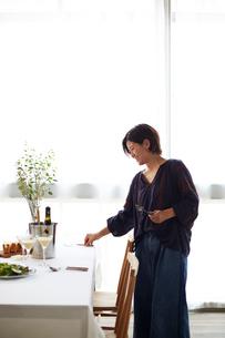 ホームパーティーのテーブルセッティングをする女性の写真素材 [FYI01464038]