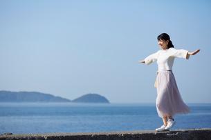 堤防の上を歩く女性の写真素材 [FYI01464046]