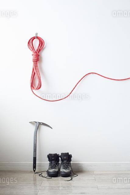 白い壁に掛けて伸ばした登山用のロープとその下に置いたピッケルと靴紐がほどけたトレッキングシューズの写真素材 [FYI01464069]
