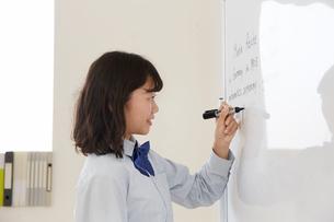 ホワイトボードに英語を書く女子高生の写真素材 [FYI01464091]