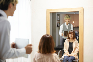 客に鏡で後ろ姿を見せる美容師の写真素材 [FYI01464119]