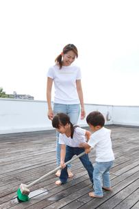 屋上を掃除する家族の写真素材 [FYI01464148]