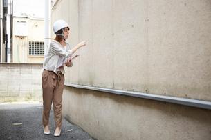 ヘルメットを被り書類を持ちながら点検をする女性の写真素材 [FYI01464155]