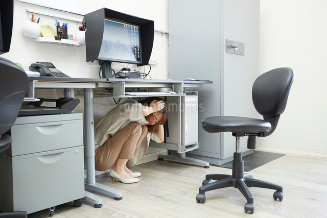 オフィスの机の下に隠れる女性の写真素材 [FYI01464160]