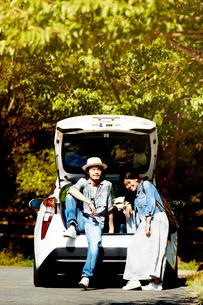 白い車のトランクを開けて話す男女の写真素材 [FYI01464166]