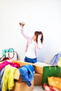 箱から出る服や鞄などが散らかった部屋と財布を持つ女性の写真素材 [FYI01464168]