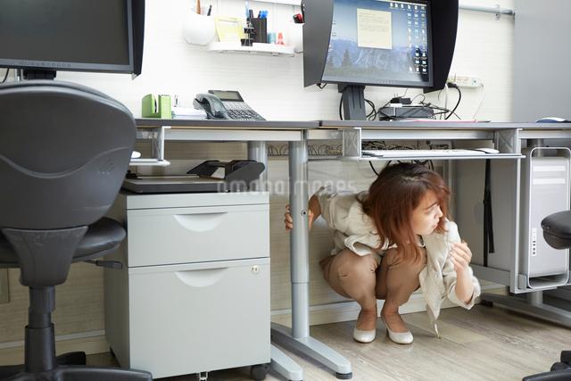 オフィスの机の下に隠れる女性の写真素材 [FYI01464175]
