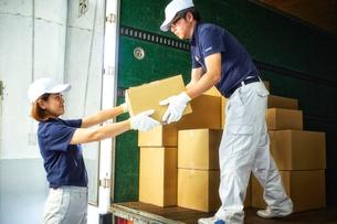 トラックから段ボール箱を積み降ろす作業服の男女の写真素材 [FYI01464181]