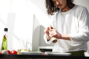 料理に胡椒をかける男性の写真素材 [FYI01464208]