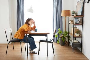 自宅にいるときに地震がきて怯える女性の写真素材 [FYI01464224]