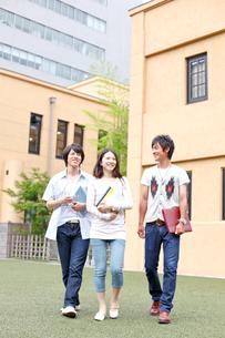 キャンパスを歩く3人の大学生の写真素材 [FYI01464242]
