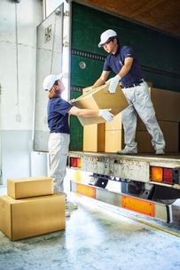 トラックから段ボール箱を積み降ろす作業服の男女の写真素材 [FYI01464243]