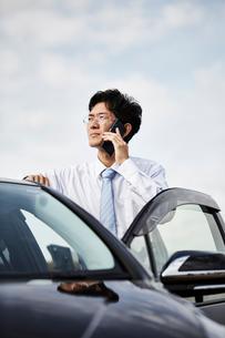 車の横に立ち電話をかける男性の写真素材 [FYI01464252]