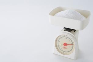 白い背景に置いてある砂糖がのった計りの写真素材 [FYI01464258]