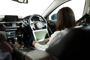 自動運転車に乗ってパソコンをする女性の写真素材 [FYI01464267]