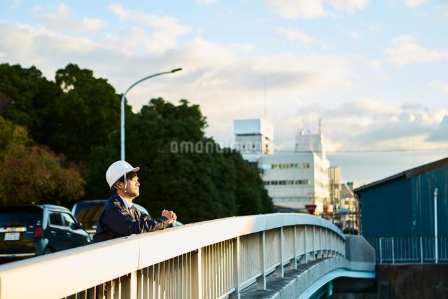橋の上から遠くを見ている作業服とヘルメットの男性の写真素材 [FYI01464270]