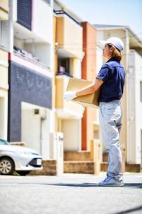 住宅街で段ボールを抱えてたたずむ作業着の女性の写真素材 [FYI01464271]