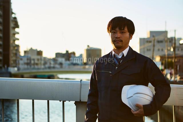 ヘルメットを脇に抱え立っている作業服の男性の写真素材 [FYI01464272]
