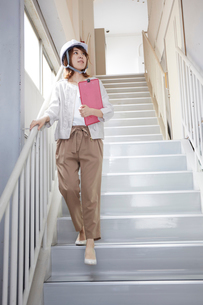 ヘルメットを被り書類を持ちながら階段を下りる女性の写真素材 [FYI01464302]