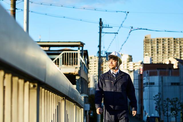 橋の上を歩く作業服とヘルメットの男性の写真素材 [FYI01464336]