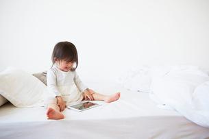 ベッドの上でダブレットを持って悲しい顔をする赤ちゃんの写真素材 [FYI01464341]