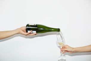 シャンパンを注ぐ男性とグラスを持つ女性の手元の写真素材 [FYI01464342]