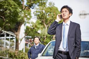 車の横に立つ男性と電話をかける男性の写真素材 [FYI01464348]