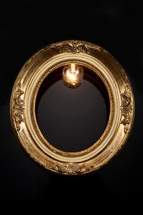 黒い背景の上にある楕円のフレームと電球の写真素材 [FYI01464357]