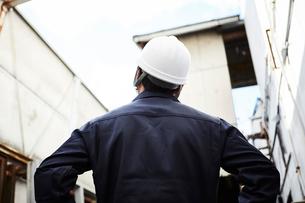 上を見上げている作業服とヘルメットの男性の写真素材 [FYI01464368]