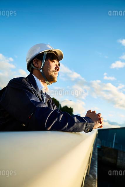 遠くを見ている作業服とヘルメットの男性の写真素材 [FYI01464376]