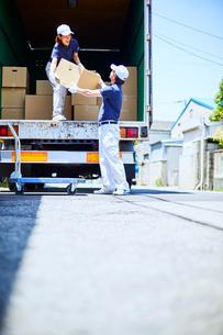路上でトラックに段ボールを積み込む作業服の男女の写真素材 [FYI01464380]