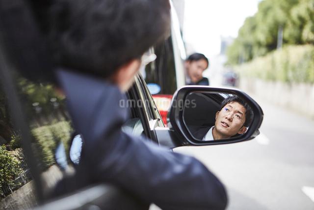 車の窓から顔を出しバックミラーに映る男性の顔の写真素材 [FYI01464399]