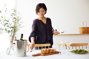 ホームパーティーのテーブルセッティングをする女性の写真素材 [FYI01464403]