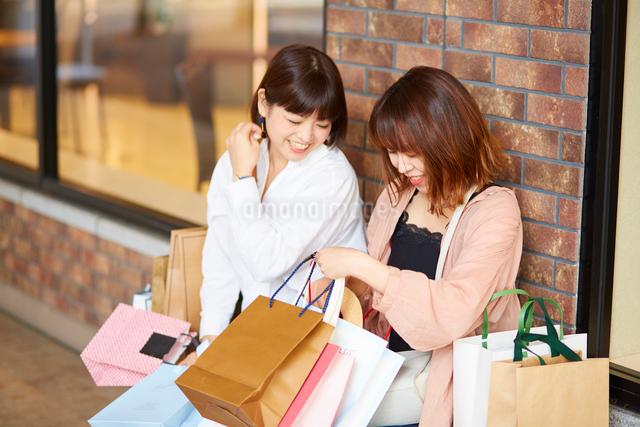 たくさん買い物をしてベンチに座る女性の写真素材 [FYI01464404]