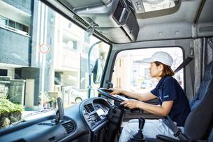 大きなトラックを運転する働く女性の写真素材 [FYI01464405]