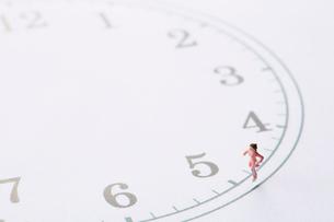 時計の文字盤の周りを走るミニチュア人形の女性の写真素材 [FYI01464418]