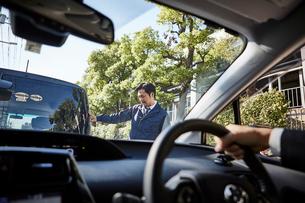 ハンドルを握る男性の手元と車の後ろを見ている男性の写真素材 [FYI01464435]